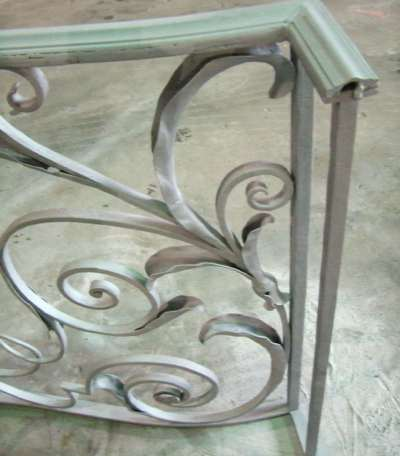Custom blacksmith recreation of leaves welded back into place. Then sandblasted.